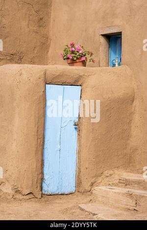 Close up detail of an adobe house with blue painted door and a pot of Geraniums. The historical Native American adobe village of Taos Pueblo, New Mexi