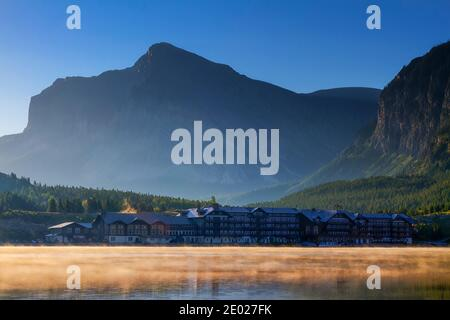 The first light of sunrise warms the landscape surrounding the Many Glacier Hotel as the mist rises from Swiftcurrent Lake to great the early risers.