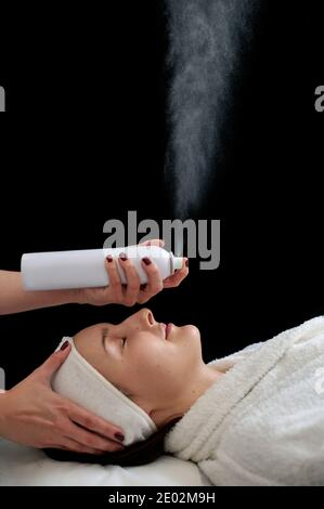 Colse up of a beautiful woman relaxing on the massage table while beautician spraying a thermal water on her face during SPA procedure.