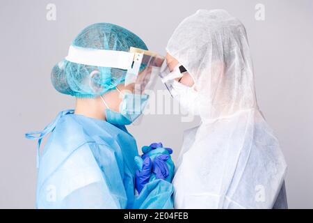 Two sad doctors comfort each other outside the intensive care unit. Pandemic and healtcare concept on white background. High quality photo