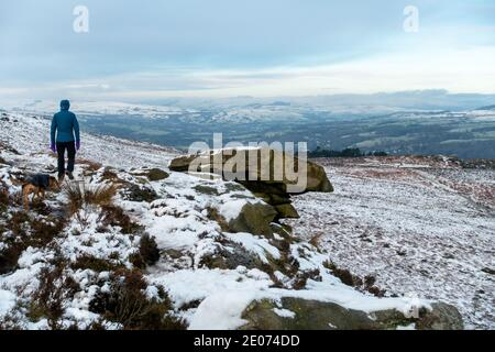 Walker walking a dog next to The Pancake Stone on Ilkley Moor on a snow covered moorland loking towards the Cow and Calf Rocks, West Yorkshire, UK - Stock Photo