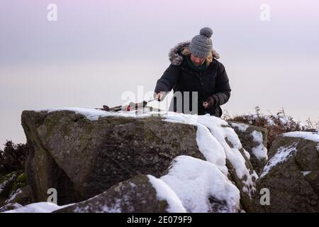 Young female artist painting, en plein air, a landscape outdoors in the snow on Ilkley Moor on a wintry day, West Yorkshire, England, UK