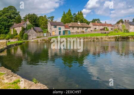 View of cottages reflecting in village pond, Tissington, Peak District National Park, Derbyshire, England, United Kingdom, Europe Stock Photo