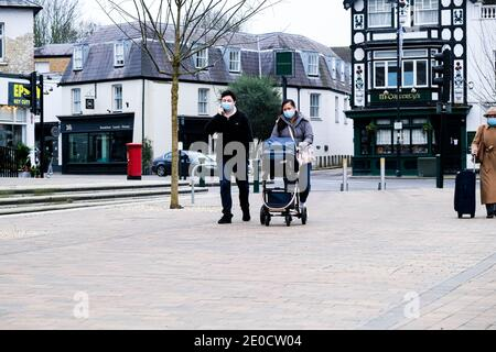 London UK, December 31 2020, Young Asian Couple With A Baby In A Pushchair Wearing Protective Face Masks During COVID-19 Tier 4 Lockdown