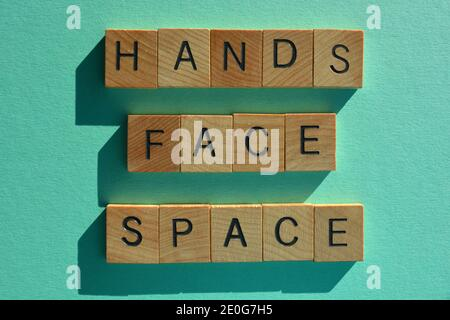 Hands, Face, Space, words in wooden alphabet letters isolated on green background - Stock Photo