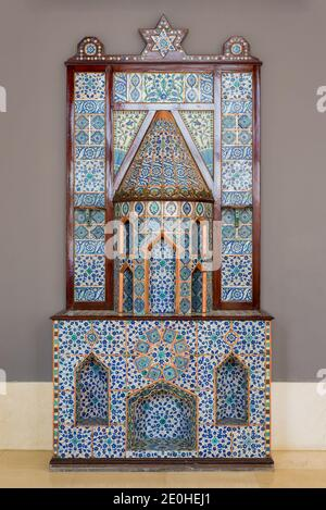 Old Ottoman era style castle shaped fireplace, decorated with floral patterns ceramic tiles from Turkish Iznik town - Stock Photo