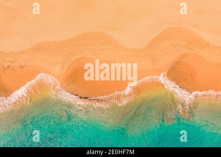 Aerial top down view of beautiful Atlantic ocean coast with crystal clear turquoise water and sandy beach, waves rolling into the shore