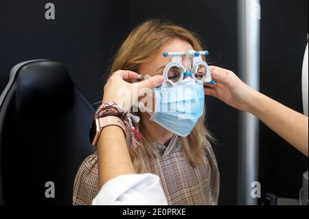 woman in an optician's having a visual exam and buying glasses.
