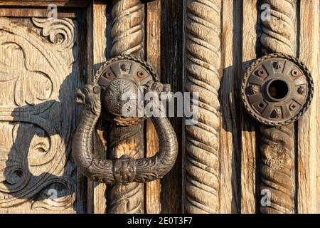 Ornamental door handle on old carved wood panel door close up detail of the historic St. Alexander Nevsky Orthodox Cathedral church in Sofia Bulgaria