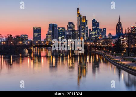 Frankfurt skyline in the evening at sunset. High-rise buildings from the financial district and river Main with reflections. Illuminated houses