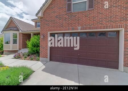 Facade of garage with brick wall and wide brown wooden door with glass panes