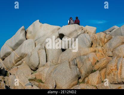 Senior Couple Sitting On The Top Of A Rock At Capo Testa In Sardinia, Italy