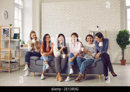 Group of happy women talking, having fun and enjoying cup of good coffee together