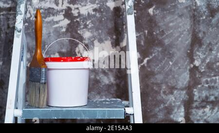A paintbrush and a bucket of paint stand on a metal stepladder against an untreated concrete wall with remnants of white paint. Background. Concept of - Stock Photo