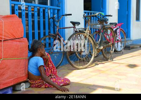 A beggar sitting outside the Indian coffee house in Pondicherry, India. - Stock Photo