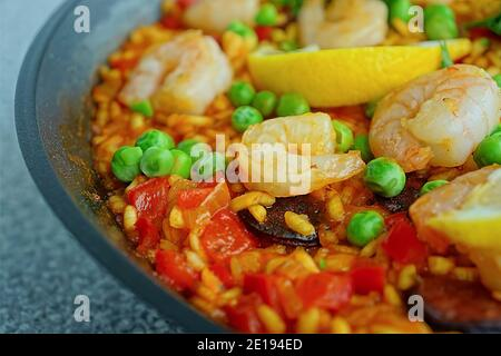 Paella is a Spanish rice dish originally from Valencia. Paella is one of the best-known dishes in Spanish cuisine. PAELLA WITH SHRIMPS AND CHORIZO. Sp Stock Photo