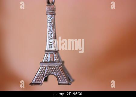 Metal keychain in the form of the Eiffel Tower in Paris, France. Souvenir from the trip close-up on orange background