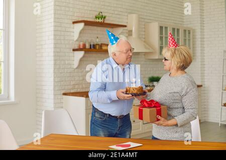 Happy elderly couple in holiday hats preparing for birthday party at home
