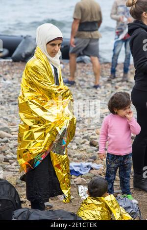 Syrian migrants fleeing the war and escaping to Europe, landing on the Greek island of Lesvos on the north coast at Efthalou and helped ashore by volu - Stock Photo