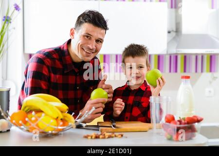 Happy father and son sitting bu the kitchen table full of fresh fruits and holding green apples in their hands. Stock Photo