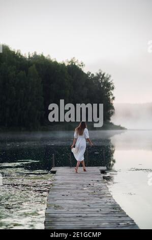 Young woman in white dress on a lake at chilly morning with a mist over water.