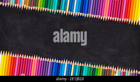 Border of colorful wooden pencils in leaning row on a blank blackboard, back to school concept.
