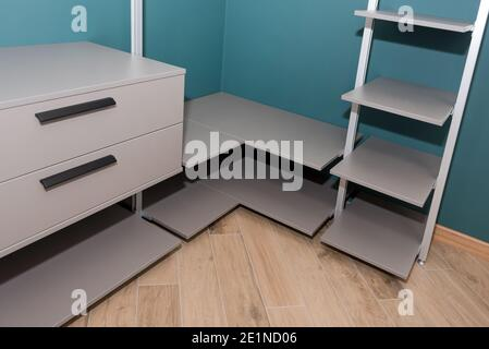 Empty walk-in closet with shelves. Dressing room Interior elements.