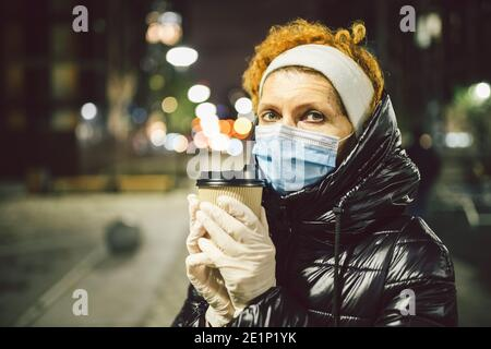 Mature Caucasian female in protective medical mask and gloves, holds takeaway coffee in hands at night city. Senior woman walk during quarantine coron