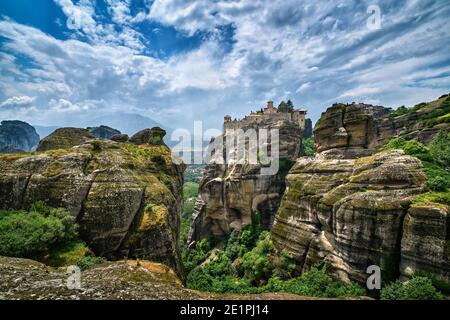 Great Meteoron monastery in rocky landscape, Meteora valley, Greece, UNESCO World Heritage, mountains, rich foliage, bright spring day. Impressive sky