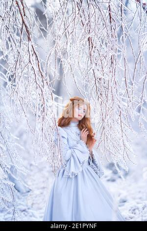 Young redhead woman, a princess, walks in a winter forest in a blue dress.