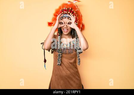 Young beautiful latin girl wearing indian costume doing ok gesture like binoculars sticking tongue out, eyes looking through fingers. crazy expression - Stock Photo