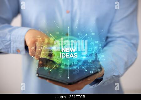 Businessman holding a foldable smartphone with NEW IDEAS inscription, new business concept