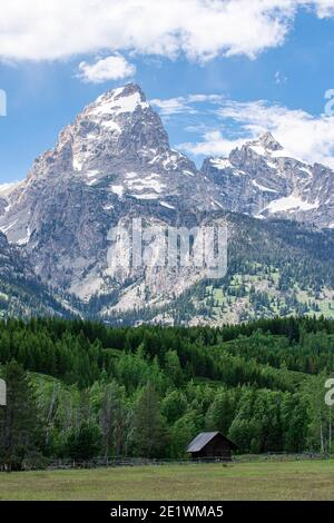 Small log cabin sits in peaceful meadow in the shadow of jagged mountain peaks of Grand Teton National Park