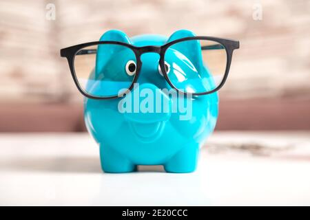 Close-up a blue piggy bank wearing black glasses on the wooden table. The symbol of saving money and wealth financial.