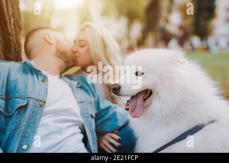 Close up of young female and male with white furry puppy are kissing while sitting under tree in autumn park
