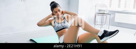 african american woman in sportswear doing elbow to knee exercise at home, banner