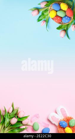 Vertical Easter composition on a pink and blue background. Top view banner with copy space flat lay greeting card.