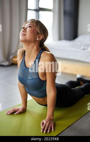 gymnast woman stretching muscles, doing sports flexibility exercises at home, wearing sportswear. female leads healthy lifestyle