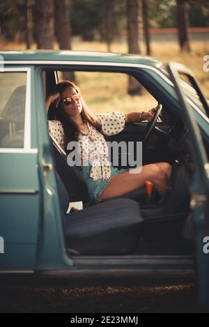 Woman in car smiling and looking at camera. - Stock Photo