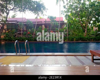 Poolside view with tropical plants and bungalow buildings - Stock Photo