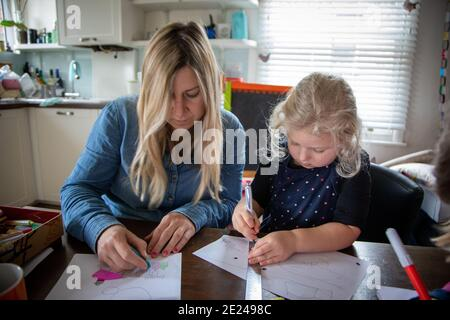 A three year old child and her mother doing school work together during the Covid pandemic, at home in the kitchen - Stock Photo