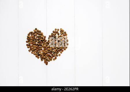 Flat lay Heart shaped cat food on white wooden background