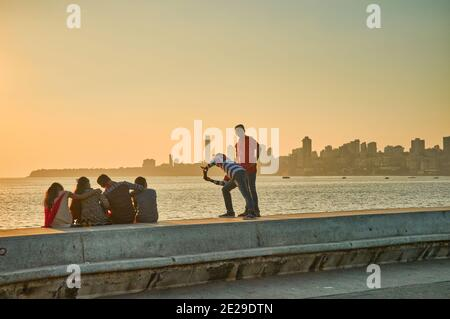 In late afternoon light, young people take photos of each other on the embankment of Marine Drive, a boardwalk by the Arabian Sea in Mumbai, India - Stock Photo