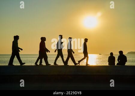 Silhouettes of sightseers, in the late afternoon sun walking on the embankment wall by the Arabian Sea at Marine Drive, Mumbai, India - Stock Photo