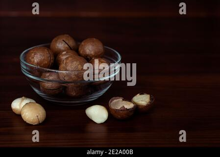 Bowls with macadamia nuts on wooden table. Shelled and unpeeled nuts