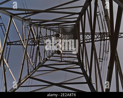 Low angle view of lattice steel power pole (also transmission tower) used to support overhead power lines in Ostfildern near Stuttgart, Germany. - Stock Photo