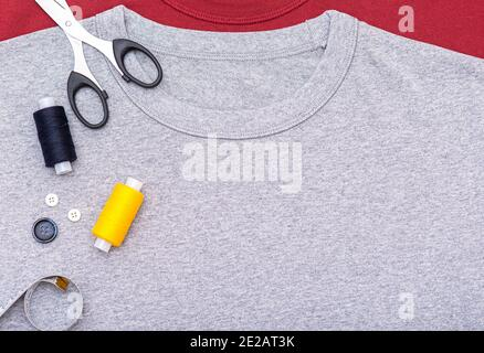 Simply composition with buttons, tape measure, scissors, spool of thread. Sewing equipment on gray t-shirt, lay out, top view.