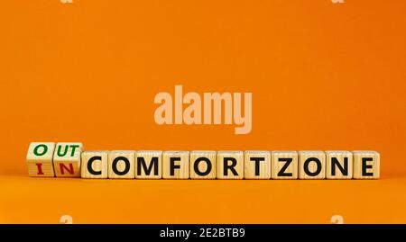 Out or in comfort zone symbol. Turned wooden cubes and changed words 'in comfort zone' to 'out comfort zone'. Beautiful orange background, copy space.