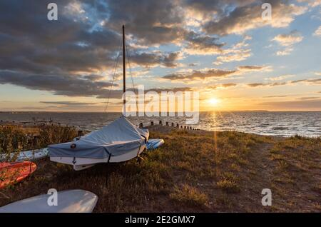 Boats on the beach at Whitstable on the North Kent coast at sunset. Stock Photo