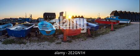 Rows of colourful boats on the North Kent coast at Whitstable with the iconic fisherman huts and works in the background. Stock Photo